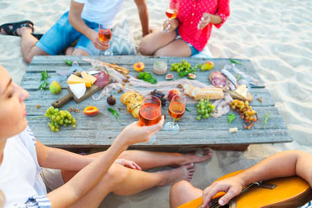 Young friends drinking rose wine on summer beach picnic. Summer vacation and party concept