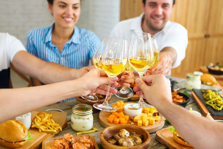 Hands with white wine toasting over served table with food. Friendship and happiness concept photo