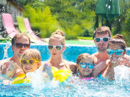 Happy big family with kids having fun in the swimming pool. Summer vacation concept photo