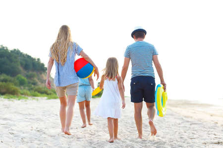 Happy young family having fun running on beach at sunset. Family traveling concept photo