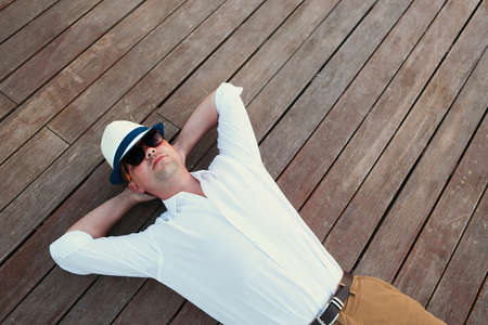 Young man lying and relaxing on wooden deck outdoor photo