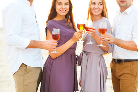 Men and women on summer beach wine party toasting by wineglasses photo
