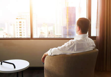 Rear view of man relaxing on chair in the hotel room photo