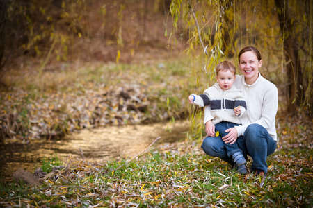 Young mother with son in autumn park. Happy family concept photo