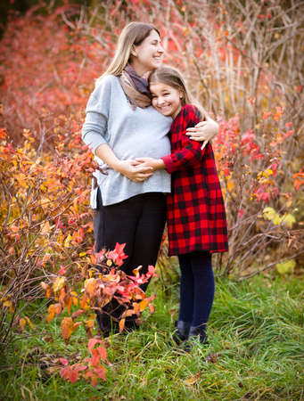 Happy young pregnant mother hugging with teen daughter in autumn park. Happy family concept photo
