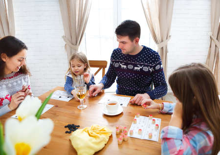 Happy young family plaing board game with two daughters photo