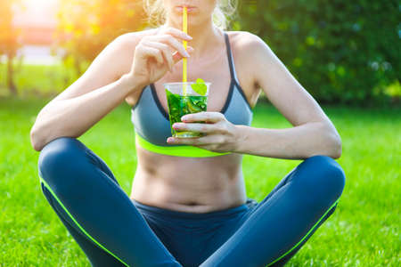 Woman drinking herbal tisane after fitness running workout on summer day. Fitness and healthy lifestyle concept photo