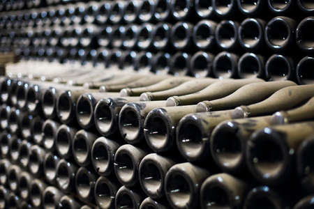 Wine or champagne bottles aged in cellar. Close up Stock Photo