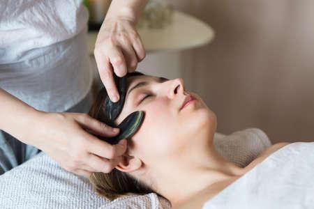 젊은 여자 아시아 아름다움 클리닉에서 얼굴 guasha 치료를했습니다.