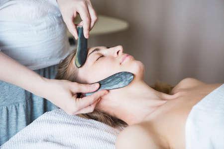 Young woman have face guasha treatment at asian beauty clinic Banco de Imagens