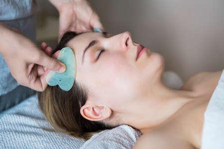 젊은 여자 아시아 아름다움 클리닉에서 얼굴 guasha 치료를했습니다. 스톡 콘텐츠 - 84973875