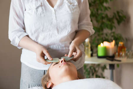 Young pretty woman face massage or beauty treatment in spa salon Banco de Imagens