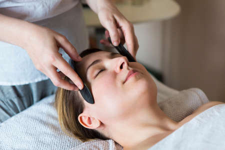 Young woman have face guasha treatment at asian beauty clinic Archivio Fotografico