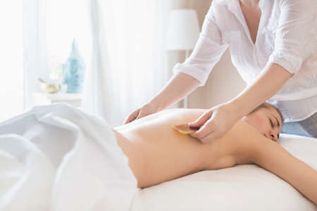 Young woman take guasha back treatment at health spa