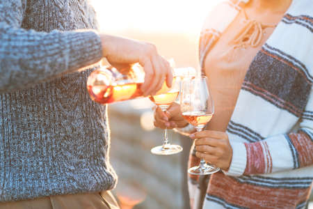 Man and woman with glass of rose wine on summer beach picnic Stock Photo