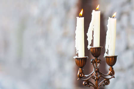 Candelabrum with three candles on grey blured background
