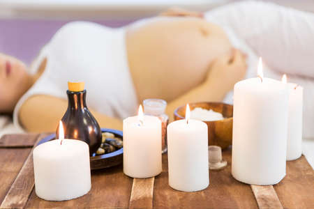 Young pregnant woman have massage treatment at spa salon