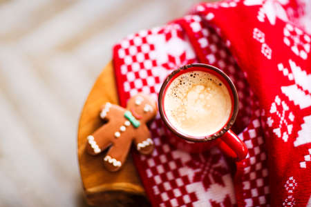 Christmas red and white background with gingerbread man, plaid and mug of coffee Stock Photo