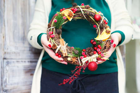 Christmas handmade wreath in young womans hands. Winter holidays celebration concept