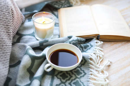 Cup of coffee, candle and book on the wooden floor
