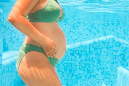 Jeune femme enceinte en bikini vert nage dans le tir sous-marin sous-marine Banque d'images - 93482529