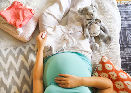 Pregnant woman is packing baby clothes for going to maternity hospital top view Stock Photo