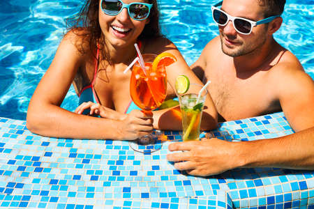 Young couple are relaxing at swimming pool party. Summer vacation concept Stock Photo