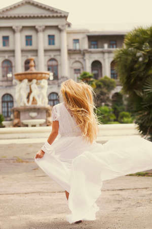 Beautiful happy running bride outdoors in park