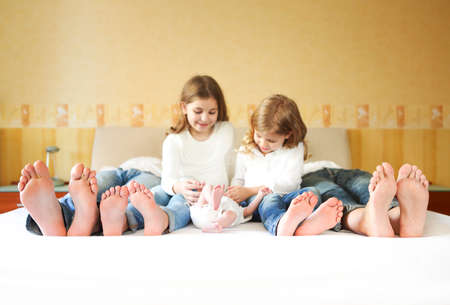 Sweet family in bed. Father, mother and three little children, close up on feet