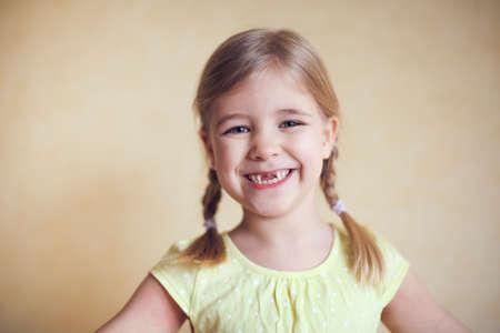 Het gelukkige verloren portret van het tandmeisje, studiospruit op de gele achtergrond Stockfoto