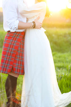 Young happy couple together hand in hand in sunset. Close up
