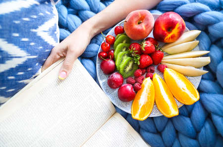 Plate with fresh fruit salad on a blue plaid and book. Woman reading the book and eating fresh fruits. Close up. Top veiw. Cozy and healthy concept