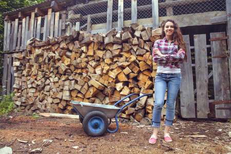 Beautiful youngcountry  woman posing on firewood background