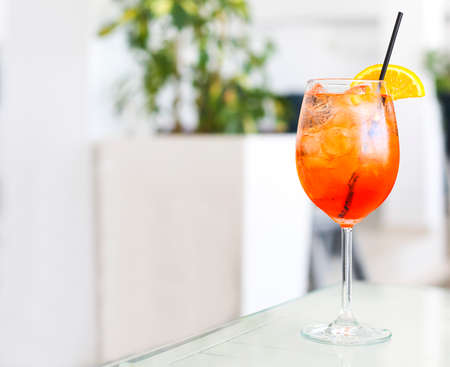 Orange alcohol cocktail with straw on white table Stock Photo