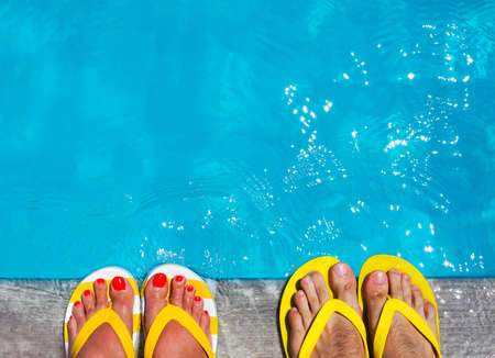 Feet in flip flops on stone background on poolside. Summer family vacation concept Stok Fotoğraf