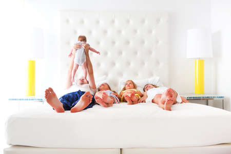 Happy playful family with three kids in the bedroom