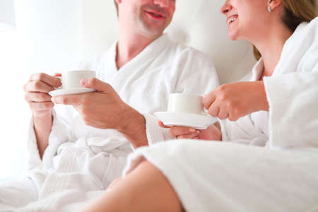 Man and woman in bathrobe drinking coffee in the bed. Morning breakfast 免版税图像