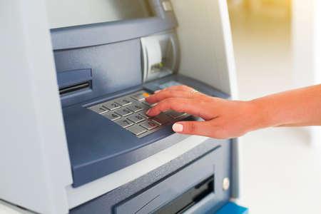 Young tourist woman using banking machine. Close up