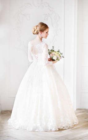 Junge schöne blonde Frau mit Blumenstrauß, der in einem Hochzeitskleid aufwirft
