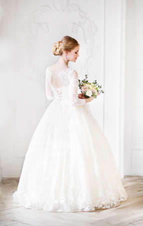 Young beautiful blond woman with bouquet posing in a wedding dress
