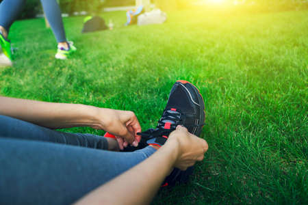 Woman lacing running shoes before workout. Close up. Fitness and healthy lifestyle concept