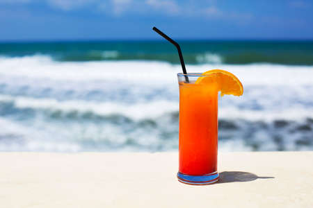 Cocktail glass on sea background. Tequila sunrise 写真素材