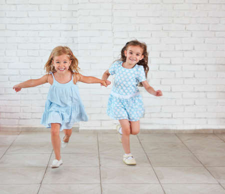 Two small girls playing and running indoors together 스톡 콘텐츠