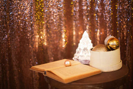 Little box with a lot of Christmas silver and golden decorations near the Christmas tree lamp and the book with copy space. Christmas holiday concept