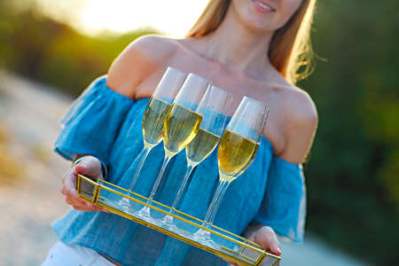 Happy woman holding tray with champagne sparkling wine into glasses outdoors at a beach. Sunset beach party Stock Photo
