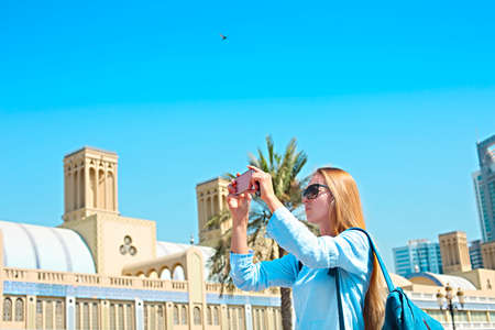 Woman taking mobile photo of the Central Souq (market) in Sharjah City, United Arab Emirates Фото со стока