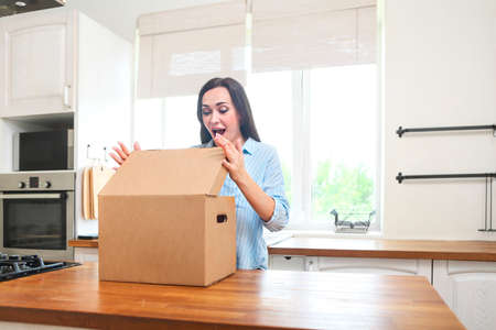 Young woman with moving box in her house moving in or out of a apartment Standard-Bild