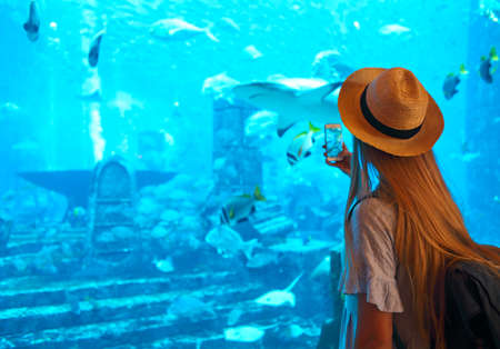 Sillouette of the woman in hat taking picture in large aquarium in Dubai