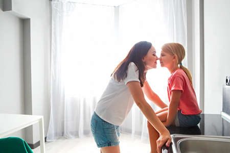 Mother and daughter nose to nose on modern kitchen background