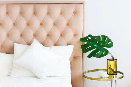 Modern bedroom with table side and pillows and coffee. Closeup Stock Photo
